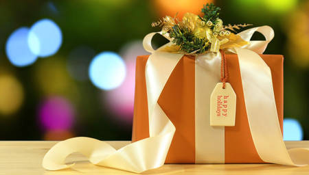 Modern gold, copper and white wrapped gift in front of bokeh lights of Christmas tree.