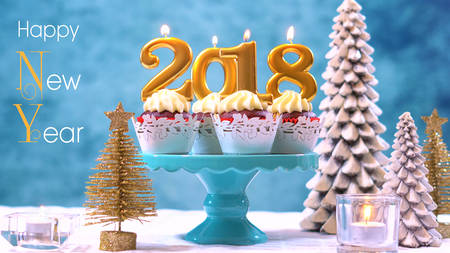Happy New Year 2018 cupcakes on a modern stylish, festive, blue gold and white Winter theme table setting, close up with Happy New Year text. Stock Photo