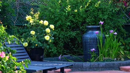 Beautiful springtime Mediterranean style courtyard garden with outdoor setting. Stockfoto