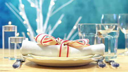 Close up of place setting with focus on napkin in elegant modern table setting for Christmas, holidays or Thanksgiving.
