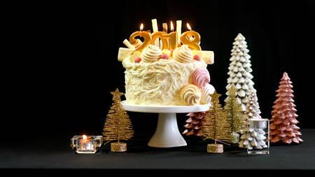 2018ハッピーニューイヤーショーストッパーケーキは、コピースペースでお祝いのテーブルの上にホワイトチョコレートフロスティング、クッキー、