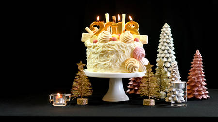2018 Happy New Year showstopper cake decorated with white chocolate frosting, cookies and candy centerpiece on a festive table, with copy space.