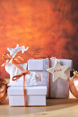 Festive Christmas modern table with copper and white gifts and ornaments on rustic background setting.
