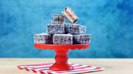 Iconic traditional Australian party food, Lamington cake, on a red, white and blue background. Stock Photo
