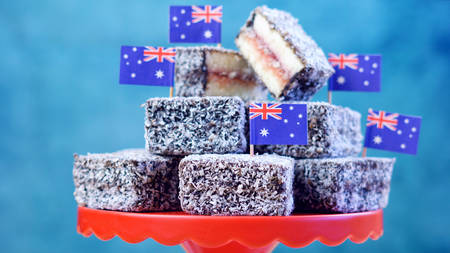 Iconic traditional Australian party food, Lamington cakes and Fairy Bread, on a red, white and blue background. Stock Photo
