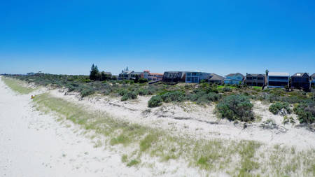Drone aerial view of wide open white sandy beach, taken at Tennyson, South Australia with nearby luxury two story homes overlooking the coast.