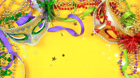 Mardi Gras overhead background with colorful masks and beads on rustic yellow wood background, with copy space. Stock Photo