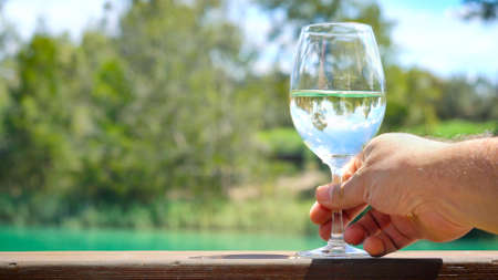 Glass of white wine on outdoor verandar rail, with reflections of Australian country setting, Barossa Valley, South Australia.