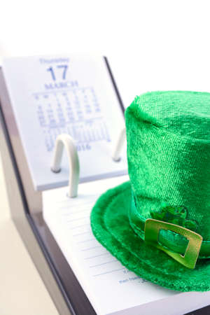 St Patricks Day calendar for March 17 with green leprechaun hat on white wood table.