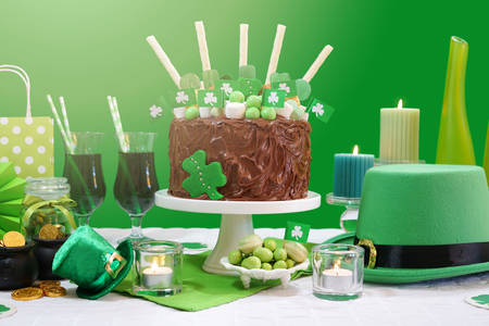 Happy St Patricks Day, March 17, green and white party table with showstopper chocolate cake decorated with candy, cookies and shamrock flags, with lens flare. Stock Photo