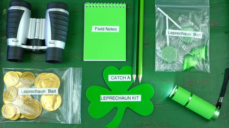 St Patricks Day Catch a Leprechaun Kit gift with binoculars, torch, field notes notepad, pencils, and candy and coins leprechaun bait bags on green wood background.