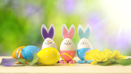 Cute Easter bunny ornaments and Easter Eggs on white table against garden background with lens flare. Stockfoto