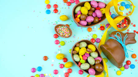 Happy Easter overhead with chocolate Easter eggs and decorations on a wood table background with copy space. Foto de archivo