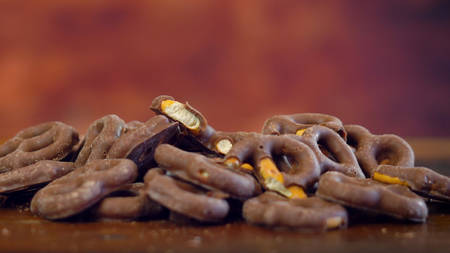 Sweet and salty chocolate covered pretzels snacks macro close up on rustic wood background with copy space. Stock Photo