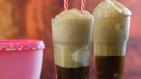 Preparing black cow cola ice cream soda floats against rustic wood background.