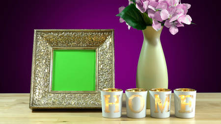 Antique photo frame with green screen and burning home candles in elegant table interiors display
