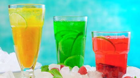 Preparing Summertime Spritzer drinks with fresh fruit, mango, berries, cucumbers and limes, with sparkling mineral water, on ice Stock Photo