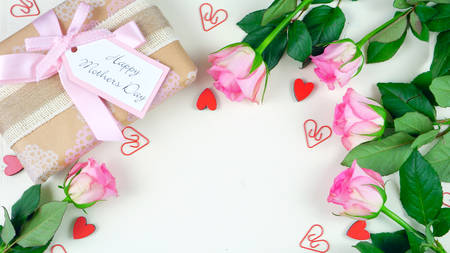 Happy Mothers Day overhead with gift and pink roses on white wood table background with copy space.