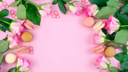 Happy Mothers Day background of pink roses and macaron cookies on pink wood table. 写真素材