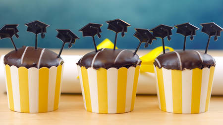 Yellow and blue theme graduation party cupcakes with cap hats toppers and decorations. Stock Photo