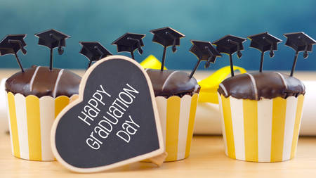 Yellow and blue theme graduation party cupcakes with cap hats toppers and decorations. Foto de archivo