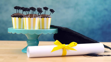 Yellow and blue theme graduation party cupcakes with cap hats toppers and decorations. Banque d'images