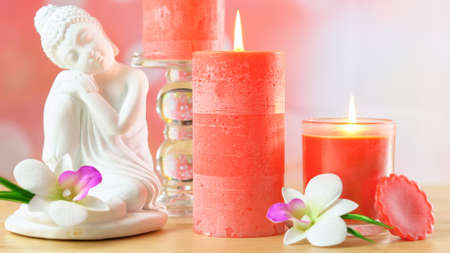 Zen style aromatherapy spa table setting with buddha, flowers and lighting perfumed candles close up. Stock Photo