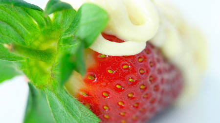 Macro closeup of fresh strawberry fruit covered in white chocolate sauce.