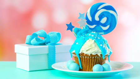 Blue theme colorful novelty cupcake decorated with candy and large heart shaped lollipops for childrens or teens birthday, Valentines or Fatherrs Day celebrations. Stock Photo