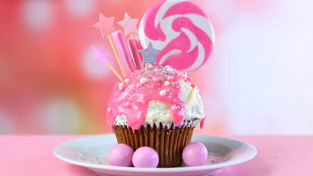 Pink theme colorful novelty cupcake decorated with candy and large heart shaped lollipop for childrens or teens birthday, Valentines or Mothers Day celebrations. Stock Photo