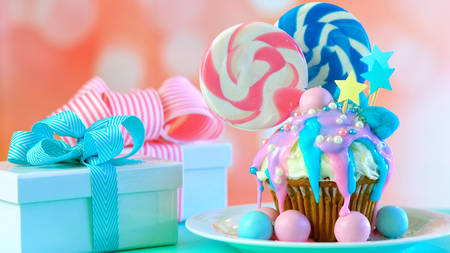 Pink and blue theme colorful novelty cupcake decorated with candy and large heart shaped lollipops for childrens or teens birthday, Valentines or Mothers Day celebrations.