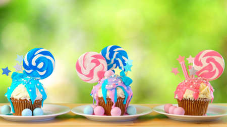 Three pink and blue theme colorful novelty cupcakes decorated with candy and large heart shaped lollipops against garden background for childrens, teens birthday or holiday celebrations. Stock Photo