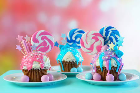 Three pink and blue theme colorful novelty cupcakes decorated with candy and large heart shaped lollipops for childrens, teens birthday or holiday celebrations. Foto de archivo