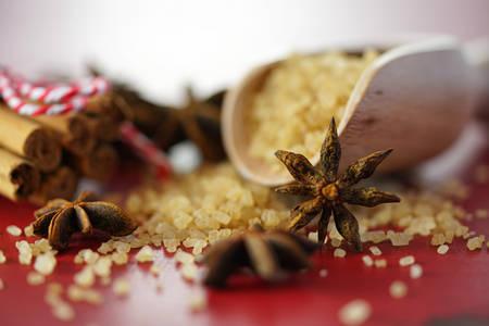 Coffee sugar, cinnamon and star anise coffee sweetener macro closeup on vintage red wood table, selective focus.