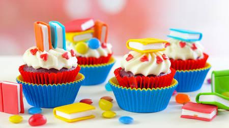 Cupcakes colorati luminosi a tema Back to School con decorazioni in topper di libri artistici di zucchero candito, celebrazioni per feste per bambini.