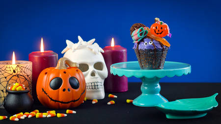 Happy Halloween candyland drip cake style cupcakes with lollipops and candy on blue background.