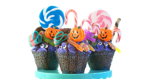Happy Halloween candyland drip cake style cupcakes with lollipops and candy on white background.