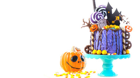 On trend Halloween candyland fantasy novelty drip cake on white background. Zdjęcie Seryjne