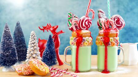 On trend Christmas freakshake milkshakes in colorful party table setting.