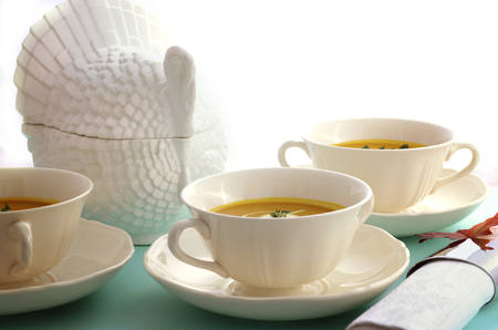 Traditional Thanksgiving pumpkin soup with white turkey tureen on pale blue table.