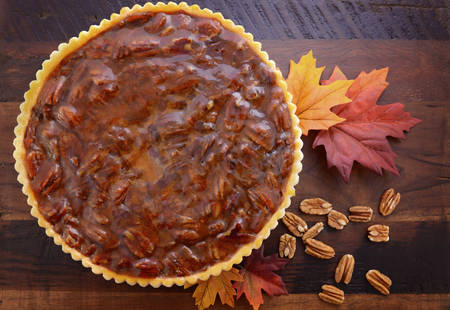 Happy Thanksgiving traditional pecan pie on vintage dark wood table and background with autumn leaves. Foto de archivo