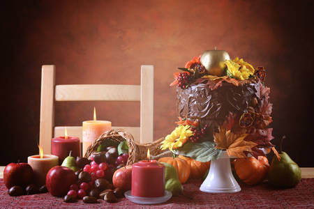 Beautiful Thanksgiving Fall table setting with Autumn theme chocolate cake, cornucopia and candles. Stock Photo