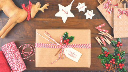 Christmas gift wrapping overhead in rustic theme with brown Kraft paper, string and natural ornaments, with applied filters.