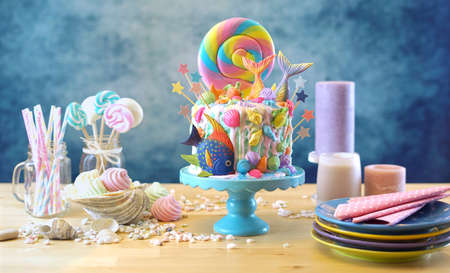 Mermaid theme candyland cake with colorful glitter tails, shells and sea creatures toppers for childrens, teens, novelty birthday and party celebrations.