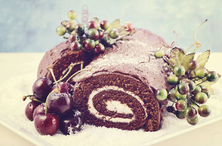 Christmas Yule Log, Buche de Noel, chocolate cake with branch, fresh cherries and festive berry decorations, with applied retro film filter.