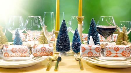 Festive Christmas lunch table in modern gold, copper, and white theme against a garden setting.