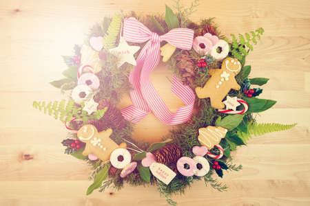 Christmas holiday wreath using fresh herbs, leaves, gingerbread, cookies, candy and gift tags with applied filters.