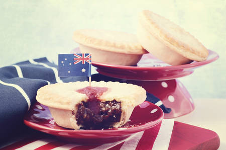 Traditional Australian Meat Pies for Australia or Anzac Day holiday party food, in red, white and blue setting, with applied vintage wash filter. 版權商用圖片