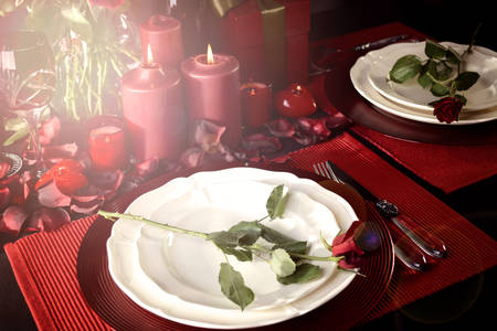 Romantic Valentines Day Table Setting for two with red roses, gift and burning candles against a black