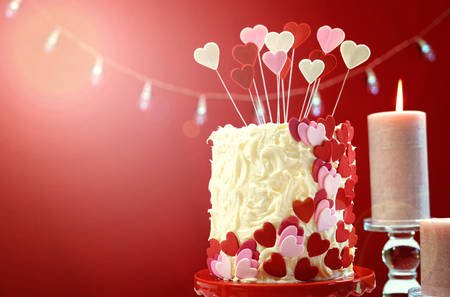 Beautiful St Valentines Day party table with showstopper red, white and pink hearts double layer cake, with white chocolate frosting, with lens flare. Foto de archivo
